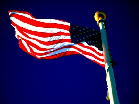 American flag unfurled against royal blue sky.