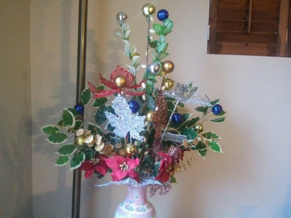 White vase with arrangement made up of silk poinsettas; silk vines; blue, gold, and silver christmas balls on sticks; and silver leaf decoration.