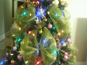 Closeup of artificial Christmas tree with lights, decorations, and large gold ribbon bows.