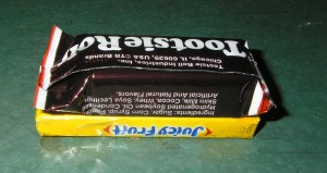 Placing Tootsie Roll on gum package.