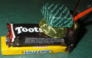 Foil wrapped mint glued on top of Reese's and addition of small candy bar and ribbon hanger.