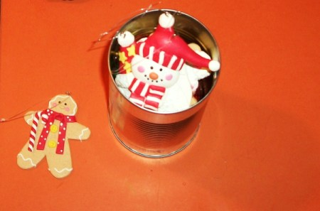Snowman Christmas ornament in tin can with label removed against orange background. Gingerbread ornament to the side.