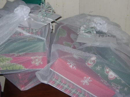 Pipe cleaner bows on mesh bag of gifts.