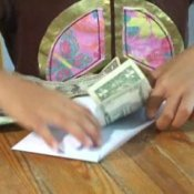 Teaching Children to Save Money, Child Putting Money in Envelope
