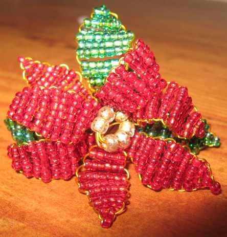 Beaded poinsettia flower with leaves.