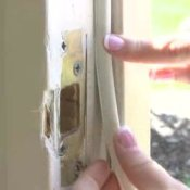 General Weatherization, Woman PUtting Weather Stripping on Window