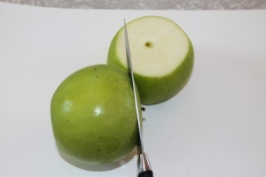 A green apple being sliced into rounds for drying.