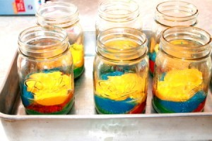 Mason jars filled with colored cake mix ready for baking.