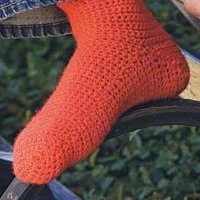A homemade crocheted sock in an orange-red color.