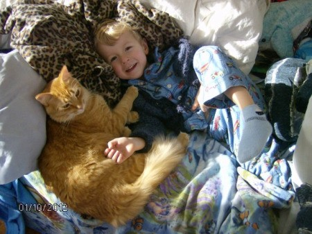 A boy lying with his orange cat, Tigger.