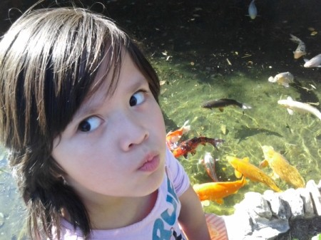 A girl in front of a koi pond at Sunken Gardens, in San Antonio, TX