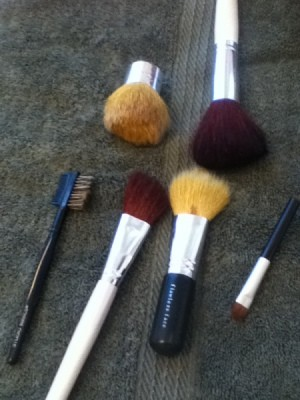 Makeup Brushes after they have been cleaned in a mason jar with marbles.