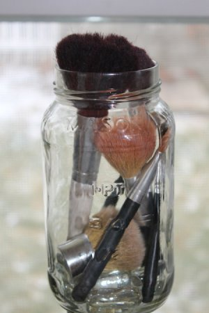 Makeup Brushes in an empty mason jar with marbles.