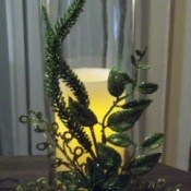 A glass candle holder with greenery.