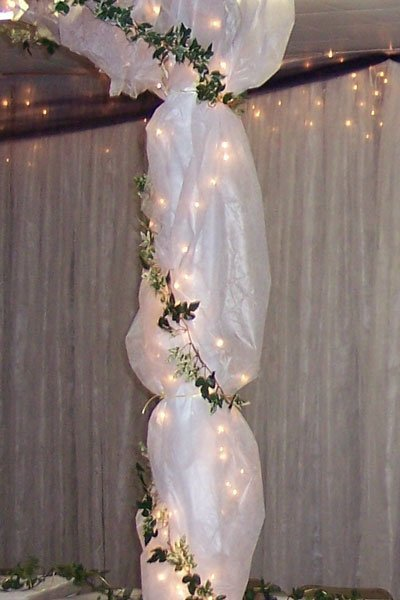 A tulle wedding decoration with greenery and white lights.