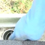 How to Clean Gutters, Man With Gloves on Cleaning Gutter