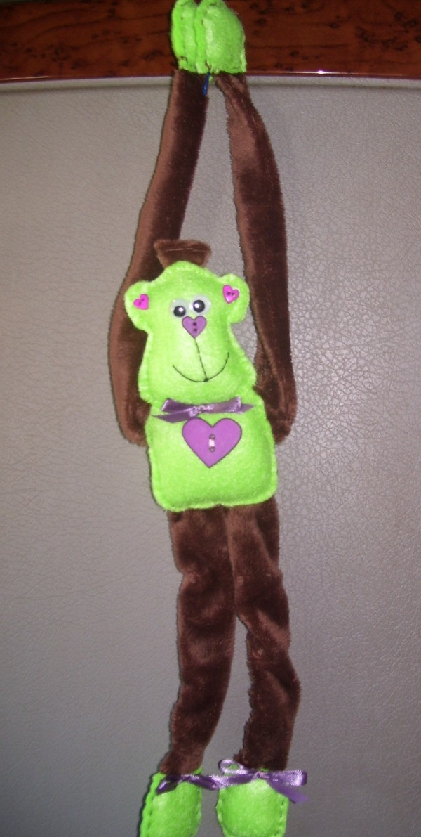 Green and brown monkey hanging by arms.