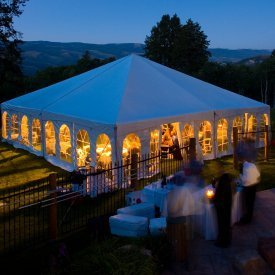 A nighttime photo of an outdoor tent wedding.
