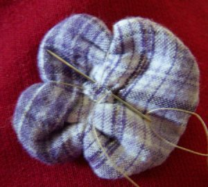 Sewing back of pincushion flower.