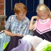 Saving Money On School Clothes - Two school age kids who are looking at their new school clothes.