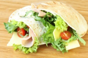 Pita sandwich with lettuce and tomato in it.