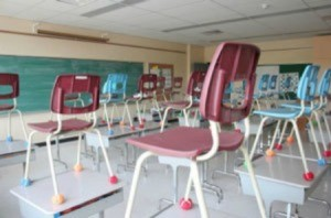 Classroom with chairs on top of desks.