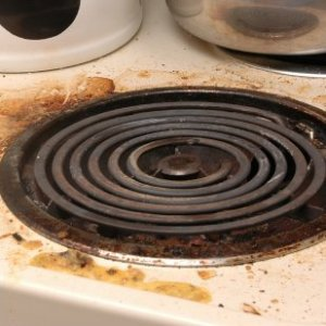 Dirty drip pan and stove top.