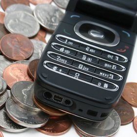 Cell phone sitting on top of a pile of change.