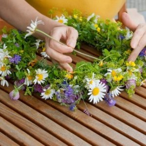 A person making a wildflower wreath.