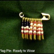 A safety pin with beads in a flag pattern.