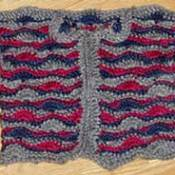 A striped crocheted baby sweater.