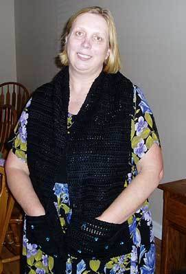 A black crocheted scarf with pockets.