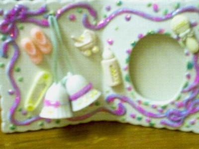 A frame for a baby girl decorated with glitter.