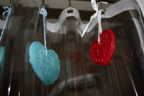 Air fresheners hanging from shower curtain rings.