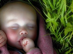 baby sleeping by grass