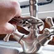 Plumber fixing a leaky faucet.