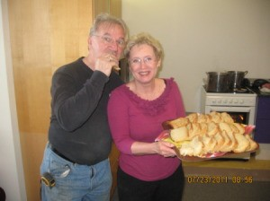 A couple with a tray holding slices of freshly baked bread.
