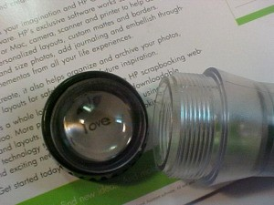 "Reusing Parts From A ""Shake"" Flashlight - the magnifier lens and cap being used to magnify words"