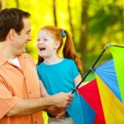 Father and daughter holding a kite.