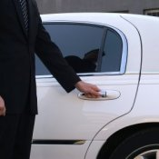 Man opening door of a white limousine.