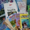 Save Money on Your Next Vacation - a pile of travel brochures.