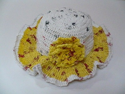 Yellow and white hat made out of plarn.