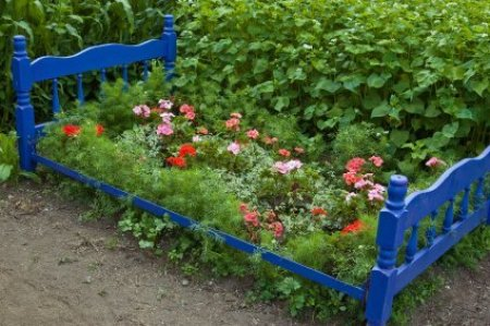 A garden bed made from an old blue bed.