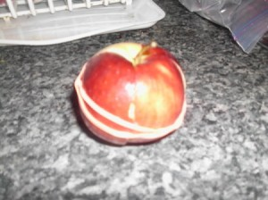 A cut apple that is held together with a rubberband to keep from browning.
