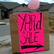 Yard sale sign in a driveway, with pink balloon.