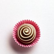 Chocolate truffle with spiral design in pink paper cup.