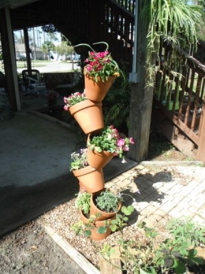 Five terra cotta pots with flowers arranged vertically on rebar.