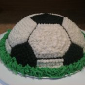 Dome shaped cake decorated like a soccer ball with green frosting along the base to mimic grass