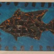 Scrap metal fish collage on wood.