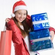 Girl in Santa hat with arm load of gifts.